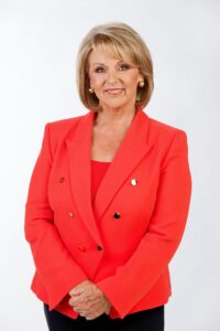 Susannah Carr standing in a red blazer.